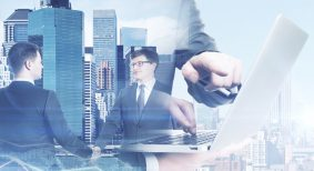 Two handsome young businessmen shaking hands and using laptop on abstract city and forex chart background. Online business. Double exposure
