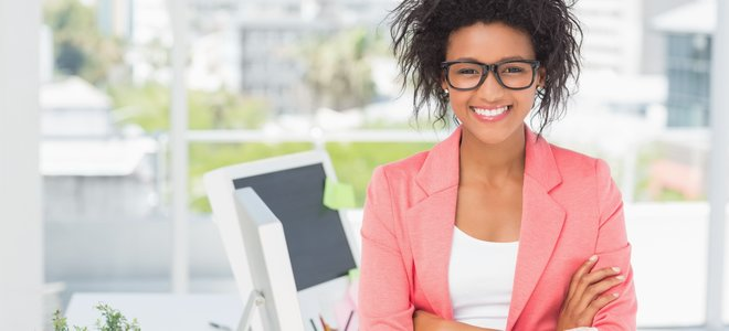 Casual female artist with arms crossed at bright office