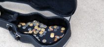 Coins in a guitar case in a street