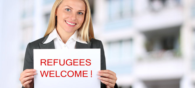 "Smiling woman holding a white banner with words "" welcome refugees"""